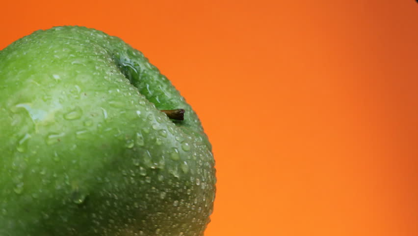 Green apple with water drops rotates on orange background - HD stock video clip