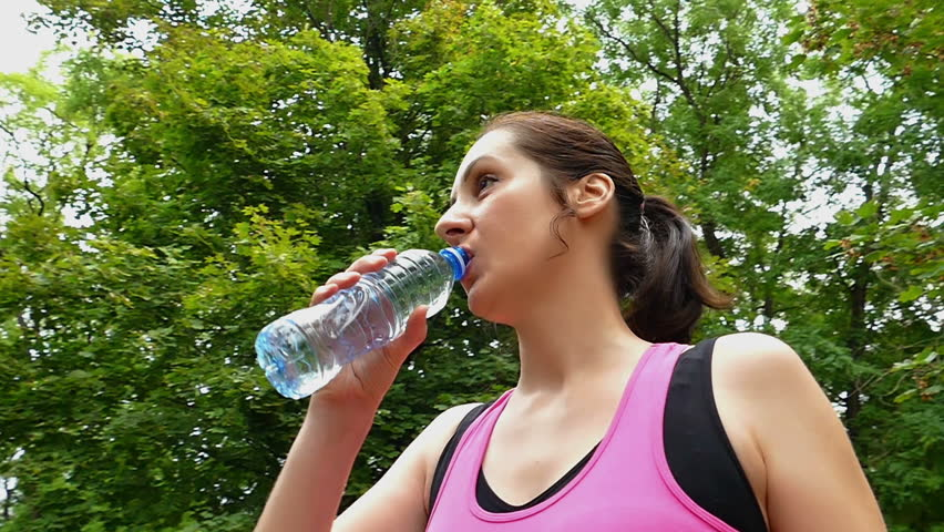 A young woman runs and drinks water in a beautiful green park in slow motion, Running and Drinking Water During Training, Slow Motion Video Clip | Shutterstock HD Video #19621549
