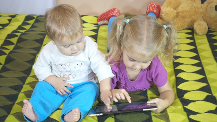 Small children using tablet pc on the bed at home. Brother and sister playing on the TouchPad tablet. | Shutterstock HD Video #19673065