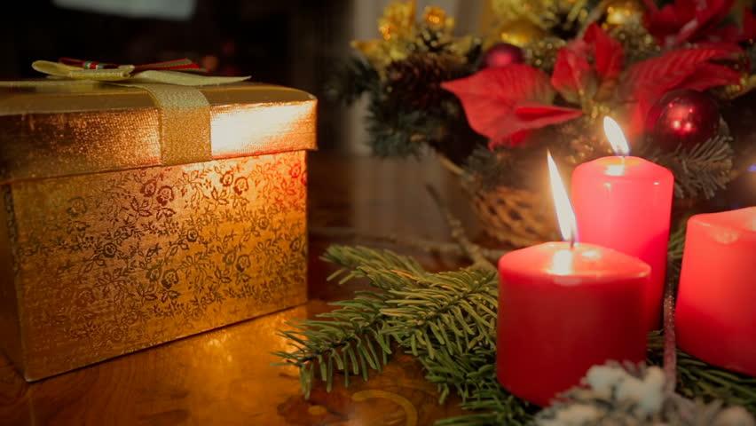 Closeup dolly shot of three burning candles and Christmas gifts at living room