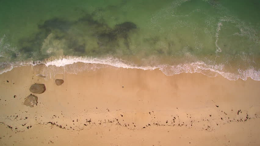 Aerial closeup - Hovering the seaside until a granite rock protrusion. Nice quiet sand beach.