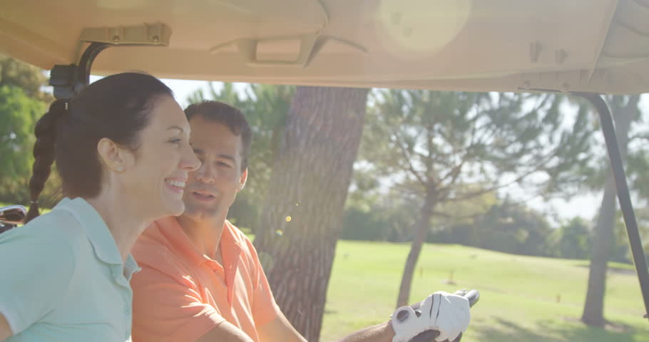 Two golfers driving in their golf buggy at golf course | Shutterstock HD Video #19730791