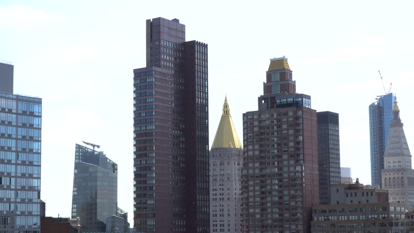 Establishing shot of midtown Manhattan New York City apartment buildings with a blown out sky in the background. Expensive NY real estate