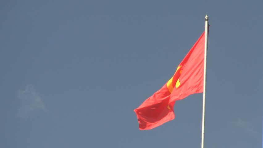 communist flag waving against blue sky in vientiane laos