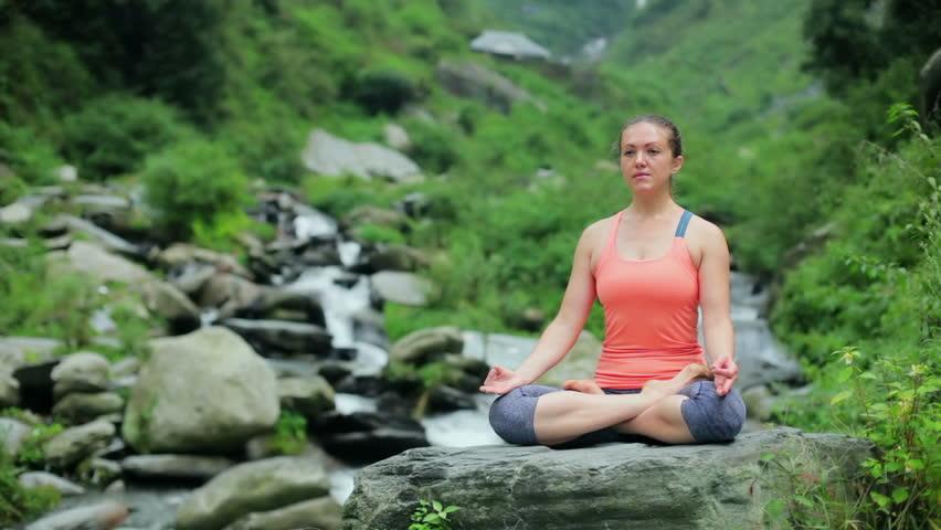Woman meditating at tropical waterfall in Lotus pose Padmasana