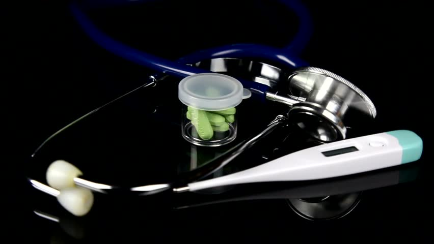 Rotating blue stethoscope with a thermometer and green pills | Shutterstock HD Video #19936936