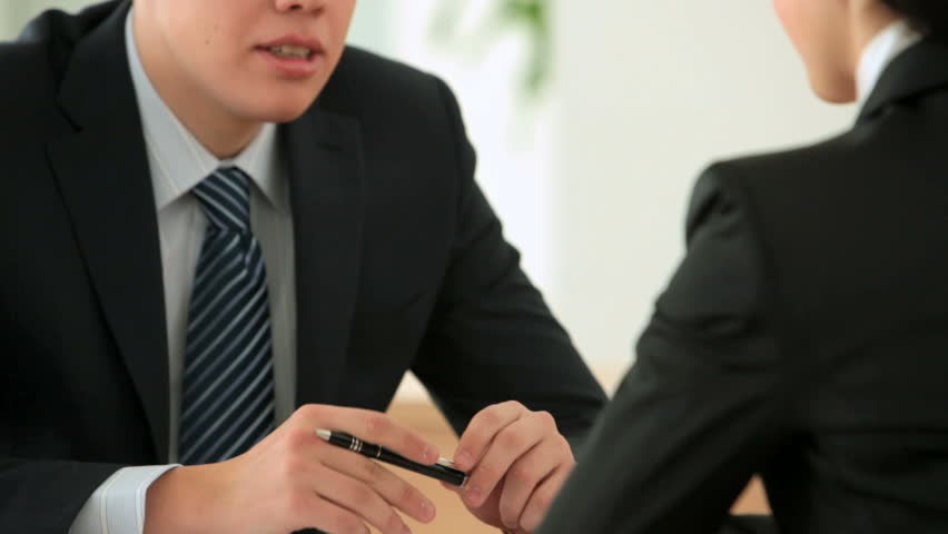 Young man interviewing a candidate for vacant position and taking notes