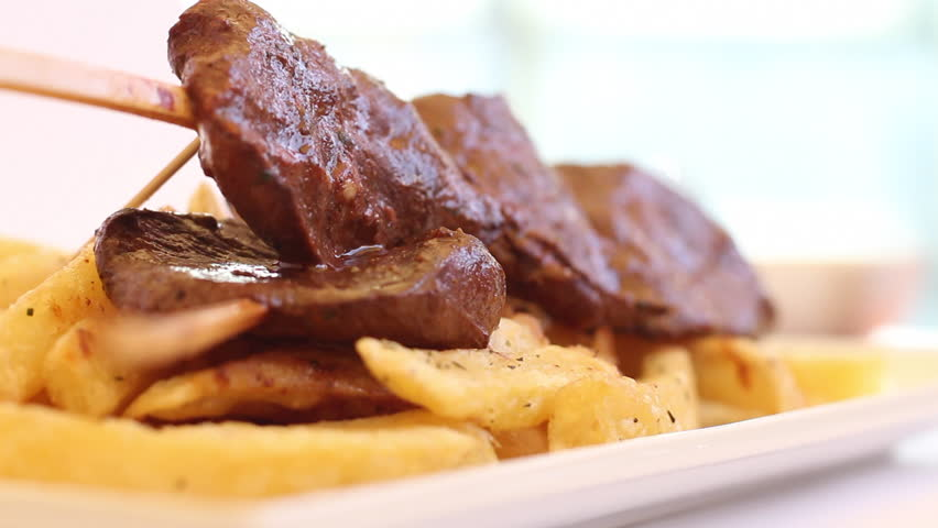 "Appetizing hot heart beef peruvian dish called ""anticucho"" with fries. Selective focus."