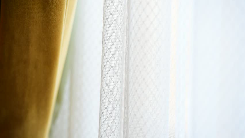 Detail with a yellow velvet window curtain shot against outdoor light | Shutterstock HD Video #20106190
