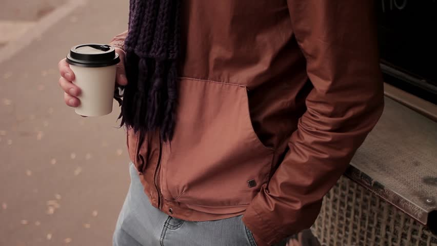 Young man with knitted scarf standing near the coffeeshop drinks coffee out of paper cup close up pan up | Shutterstock HD Video #20234530