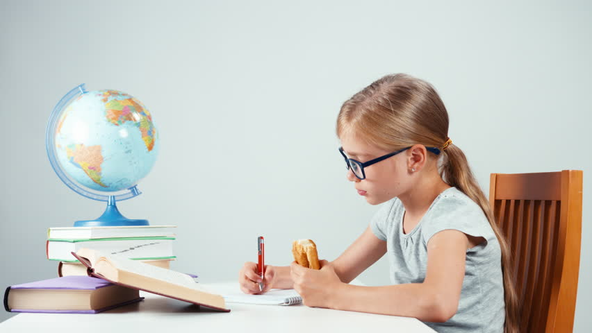 School girl writing in her notebook and eating croissant. Child sitting at desk isolated on white background. Thumb up. Ok | Shutterstock HD Video #20265670