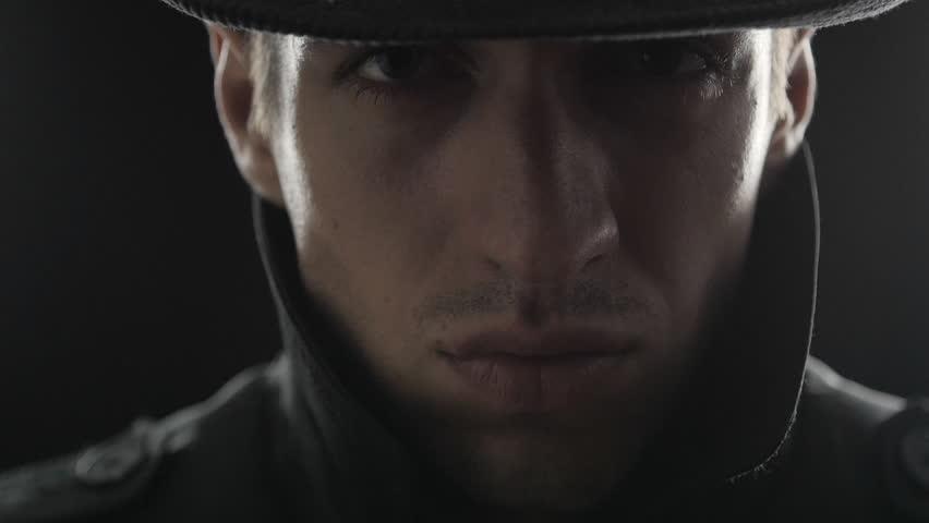 Close up Portrait of gangster in a hat and a black cloak with a gun | Shutterstock HD Video #20345401