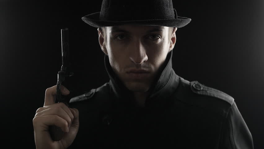 Portrait of a gangster in a hat and a black cloak threatens with weapon. Mafioso aiming a gun at the camera | Shutterstock HD Video #20345419