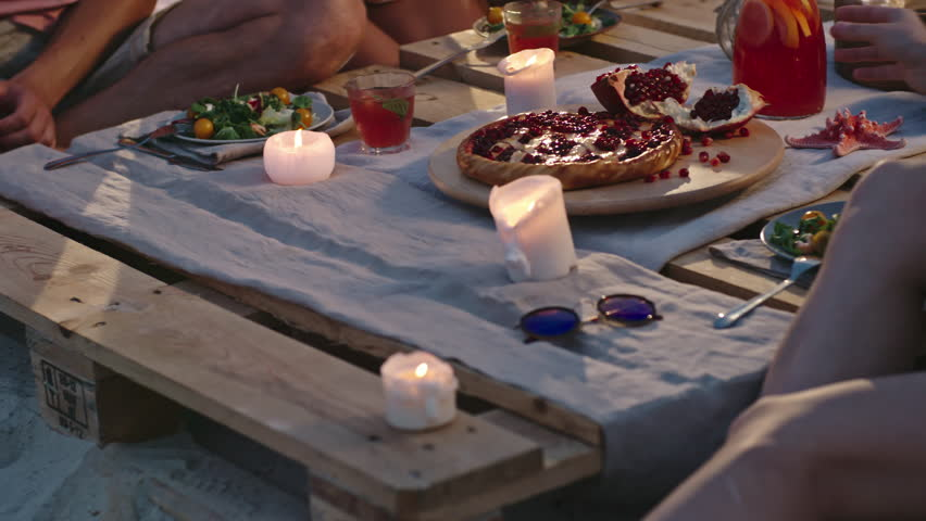 Group of young people having dinner at wooden beach table served with fruits, salads and tropical drinks and burning candles on it