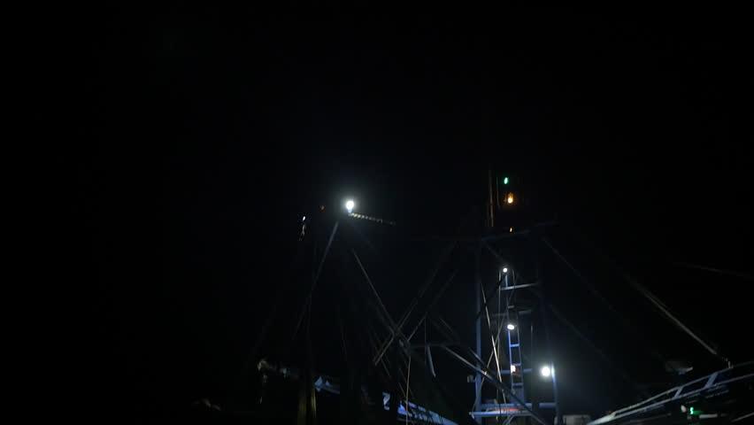 Pan up on shrimping trawler sailing out to sea to fish at night.