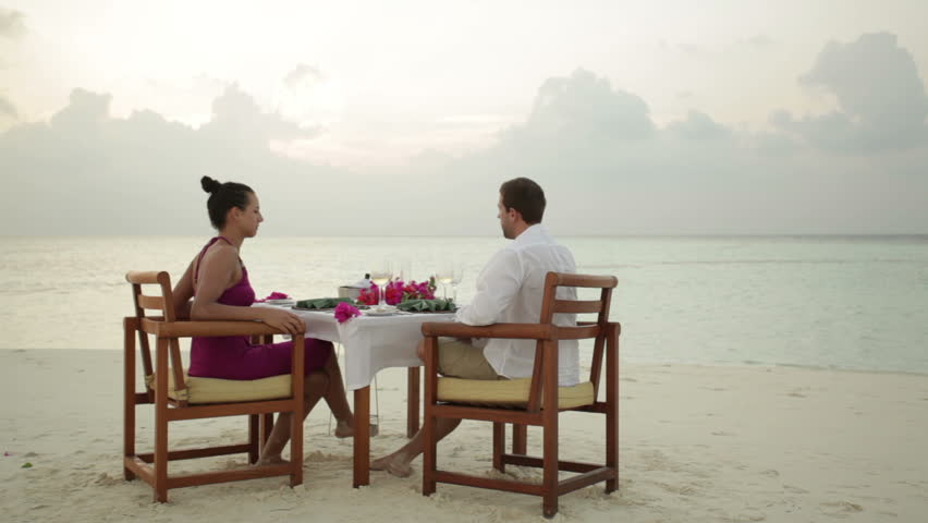young couple cheering with wine during romantic dinner on sandy beach