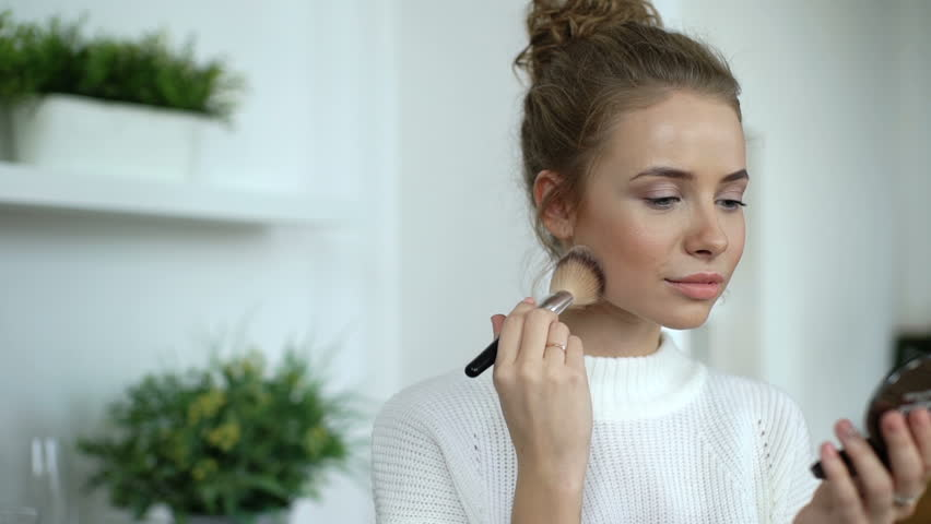 Beauty woman applying makeup. Beautiful girl applying cosmetic with a big brush. Girl gets blush on the cheekbones. Powder, rouge. Slow motion. | Shutterstock HD Video #20595898
