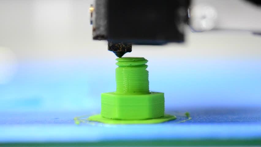 3D printer makes or printing bolt model, screw green colour close-up