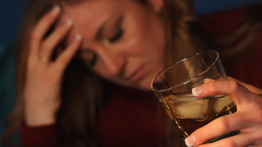 Woman drinking alcohol. Glass in sharp focus. Shallow DOF.