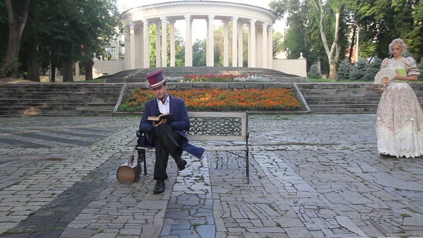 Couple in retro suit and dress reading a book on a bench | Shutterstock HD Video #20739070