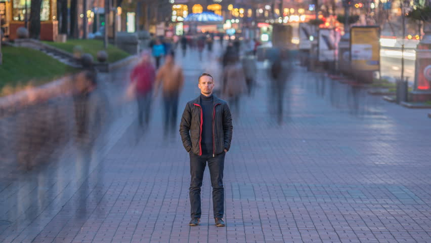The man stand in the ghost-like crowd flow. Evening to night time. Time lapse   Shutterstock HD Video #20900161
