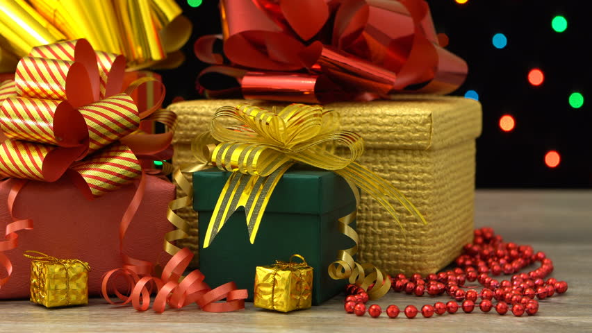 Beautiful Christmas gift boxes and decorations on a wooden floor against colorful flashing garland on a black background. Seamless loopable. | Shutterstock HD Video #20903077