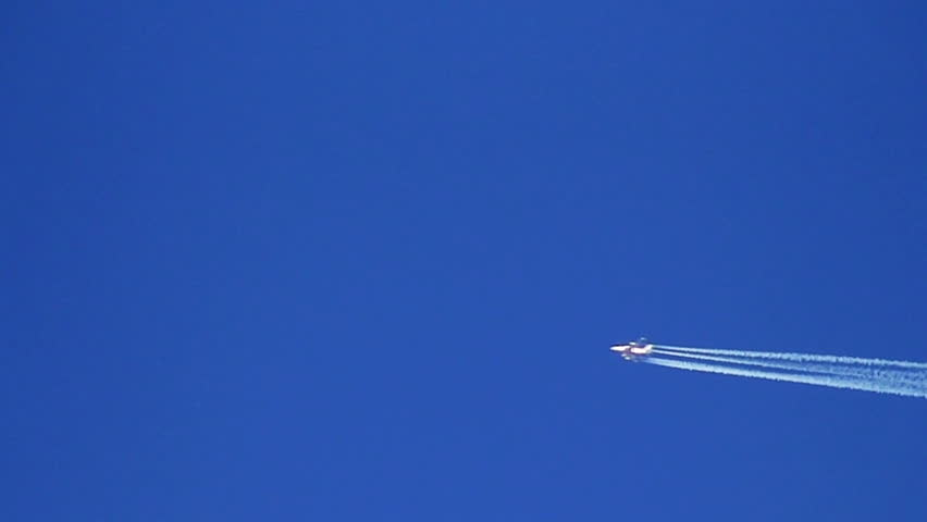 Airplane vapour trails across clear blue sky (slow motion) - HD stock video clip