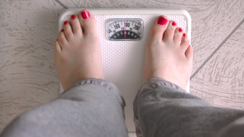 Female Standing on Weight Scale (HD). Female standing on a white generic weight scale to measure her pounds just shy of 180lbs.
