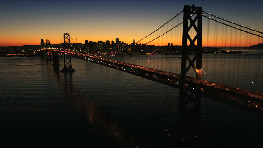 Aerial sunset view of the Oakland Bay Bridge at night with the illuminated light from traffic, San Francisco, North America - HD stock footage clip
