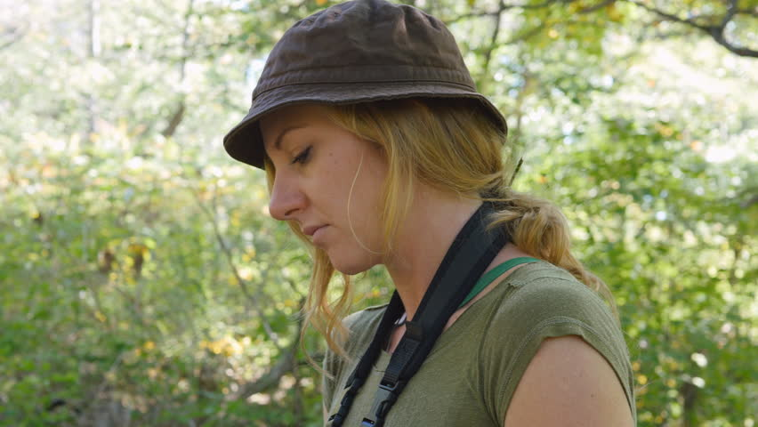 Tilt down of female birdwatcher writing with pencil in notebook.  #21330640