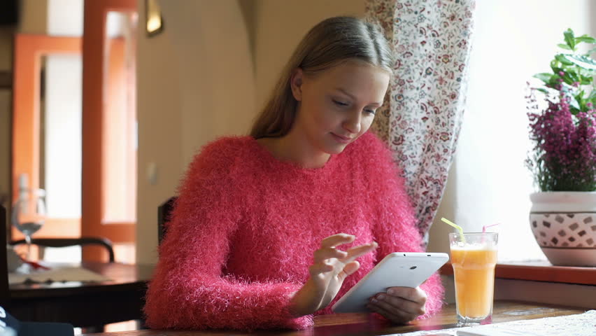 Pretty girl browsing internet on tablet while sitting in the cafe  | Shutterstock HD Video #21350665