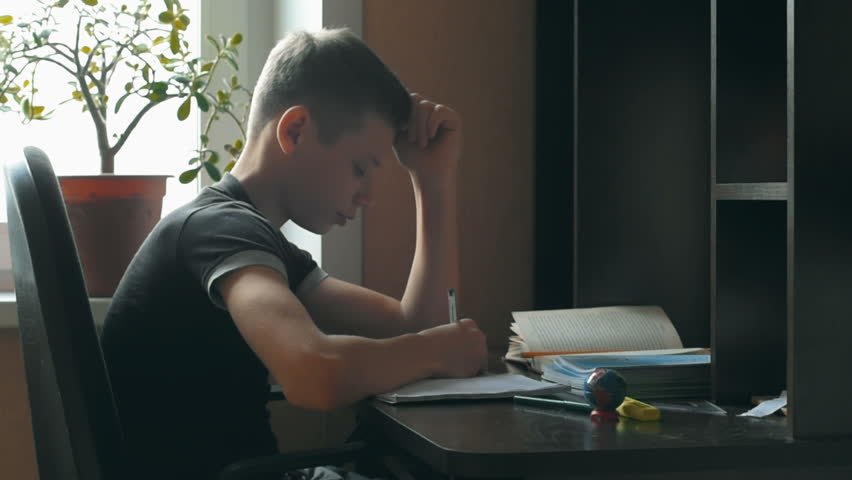 Little boy doing homework. He sits at his desk, learning to write letters. Schoolboy encircles a pre-written letters and their elements in a special notebook. On the table is a table lamp. Closeup. | Shutterstock HD Video #21555145