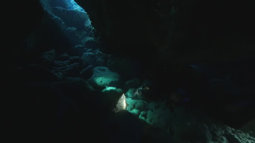 Diver in the underwater cave with sun rays and beams