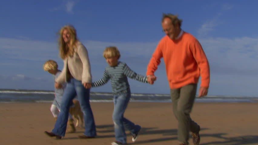 WIDE SHOT, Family with dog running hand in hand on beach