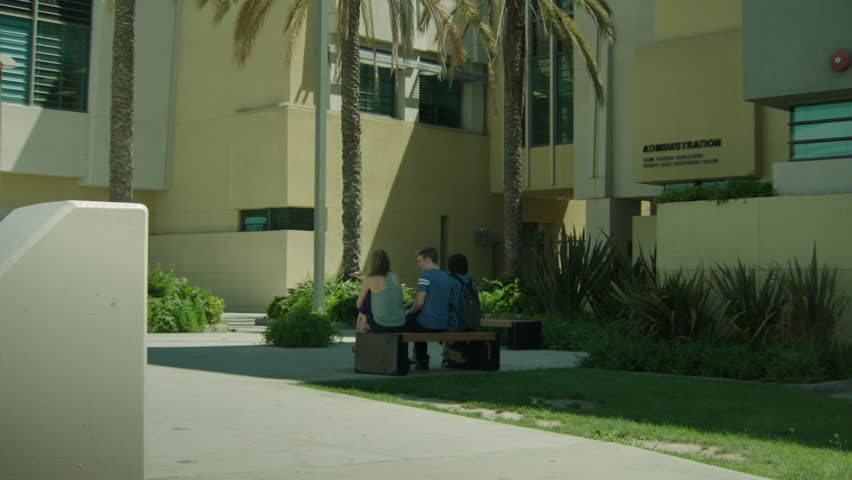 Day modern high school campus school administration building, palms 3 students sitting bench, few students through, spring summer | Shutterstock HD Video #21745612