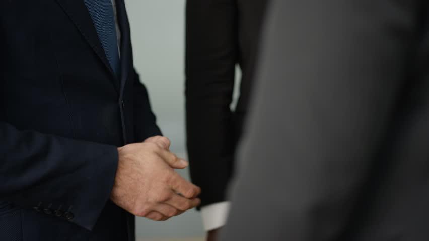 4K Cheerful businessmen shaking hands and having conversation in modern office (UK-Oct 2016)   Shutterstock HD Video #21771262