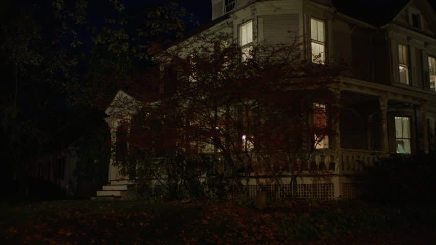 Night front then pans right along see side beige wood clapboard house , wrap around porch, back porch, bay windows, turret, dormers, autumn, fall trees, lights on, (Oct 2012)