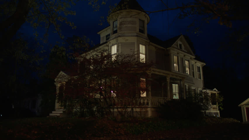 Magic Hour night then tilts up corner side beige wood clapboard house , wrap around porch, back porch, bay windows, turret, dormers, detached garage, autumn, fall trees, lights on, cloudy, (Oct 2012)