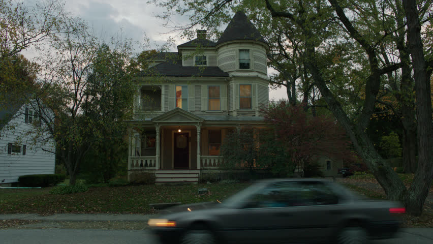 Day late day, dusk front beige wood clapboard house , wrap around porch, bay windows, turret, dormers, red screened door, autumn, fall trees, breezy, lights on, cloudy, stormy (Oct 2012)