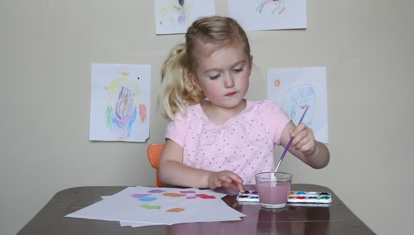 Young child drawing with crayons while sitting at desk - HD stock video clip