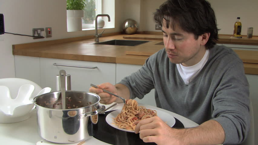 MEDIUM SHOT PAN OF A MAN EATING PASTA