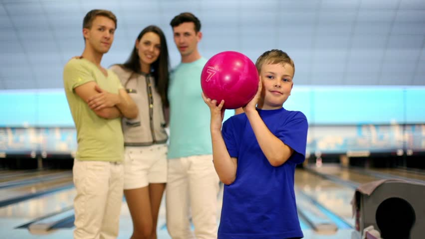 Students team watch on little boy throws bowling ball