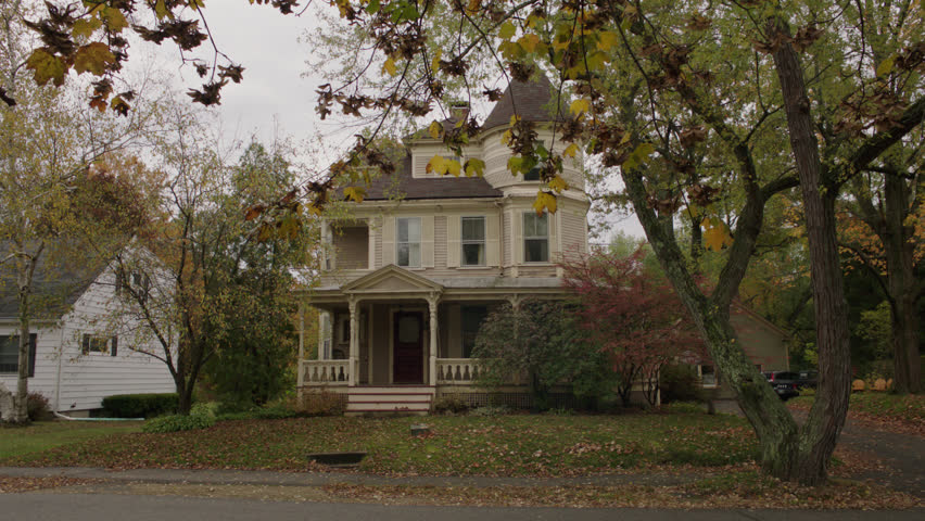 Day beige wood clapboard house , wrap around porch, bay windows, turret, dormers, red screened door, autumn, fall trees, small move left, (Oct 2012)