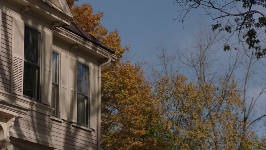 Day right pans left corner upstairs windows beige wood clapboard house , dormers, autumn, fall trees, (Oct 2012)
