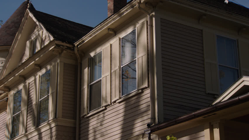 Day from back then pushes windows up side beige wood clapboard house , dormers, autumn, fall trees, (Oct 2012)