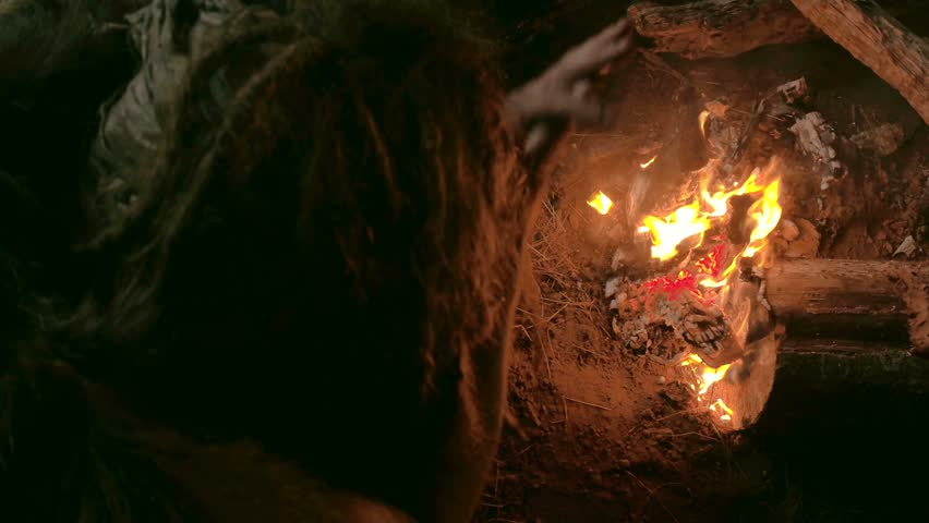 Neanderthal man warms his hands by the first bonfire in his cave