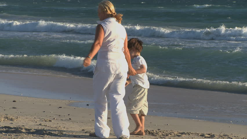 LONG SHOT PAN OF GRANDPARENTS MAKING SANDCASTLES WITH THEIR GRANDCHILDREN - HD stock video clip
