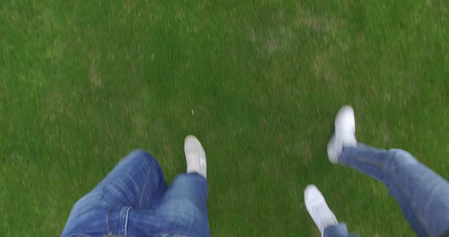 Two boy with white shoes and blue jeans are walking in the meadow. Top view. | Shutterstock HD Video #21979324
