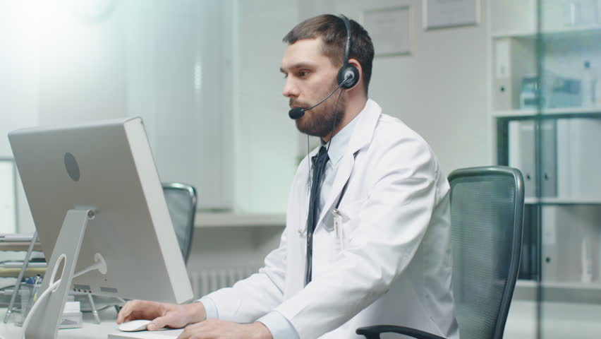 Male Doctor Consults Patients on the Internet. He Sits before His Personal Computer and Wears Microphone.  | Shutterstock HD Video #22019887