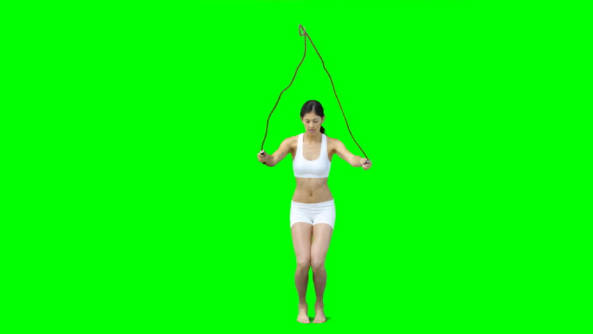 Young woman skipping against a green screen